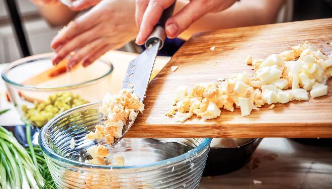 Krojenie gotowanego jajka, przygotowania do sałatki jarzynowej